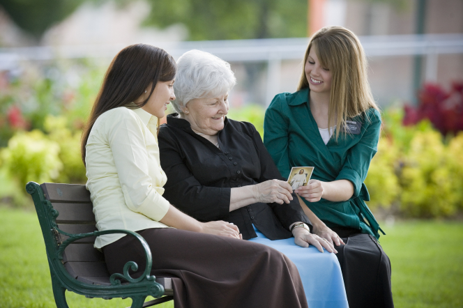 An elderly woman sitting on a bench outside between two sister missionaries, holding a pass-along card with a picture of Christ.