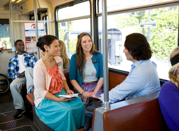 Two sister missionaries on a train, one of them holding an open Book of Mormon, talk to a man sitting across from them.