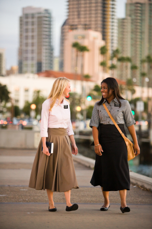 Two sister missionaries look at each other while walking down a street, with tall trees and buildings in the background.