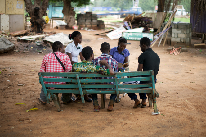 Two sister missionaries teaching a group of four teenage boys sitting on a green wooden bench in Ghana, Africa.