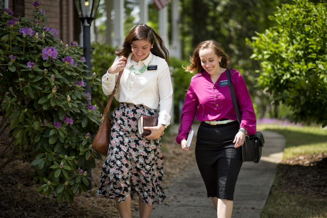 A sister missionary in a white blouse and floral skirt walking beside her companion in a purple blouse and black skirt, both carrying bags and scriptures.