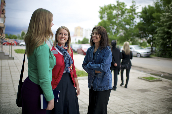 A woman with brown hair, a black dress, and denim jacket talks to two sister missionaries outside in Bulgaria.