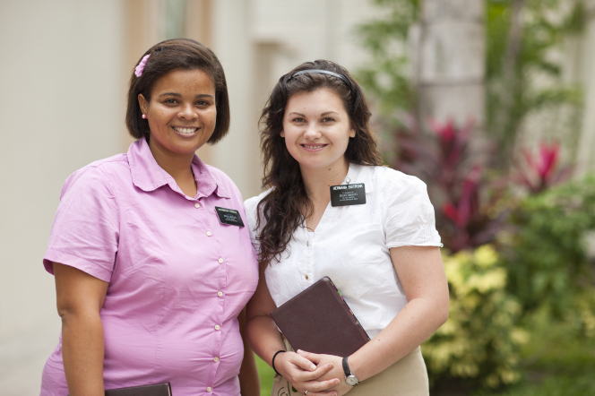 A sister missionary with short brown hair and a pink shirt standing beside her companion, who is wearing a white shirt and holding scriptures.