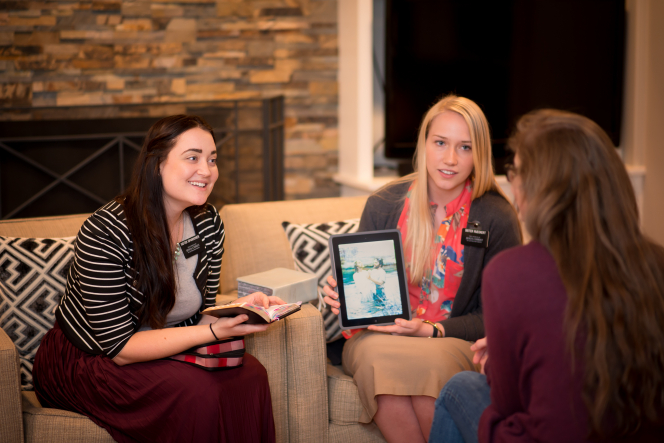 Two sister missionaries teaching a woman with long brown hair, using open scriptures and an iPad with a picture of Christ being baptized.
