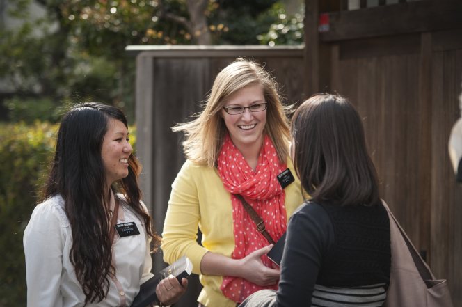A woman in Japan talking to two sister missionaries, one black-haired and one blonde, both holding scriptures.