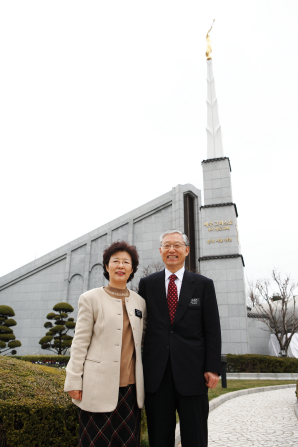 A senior elder missionary in a white shirt, red tie, and suit stands beside his wife in a brown shirt, white jacket, and black skirt outside the Seoul Korea Temple.
