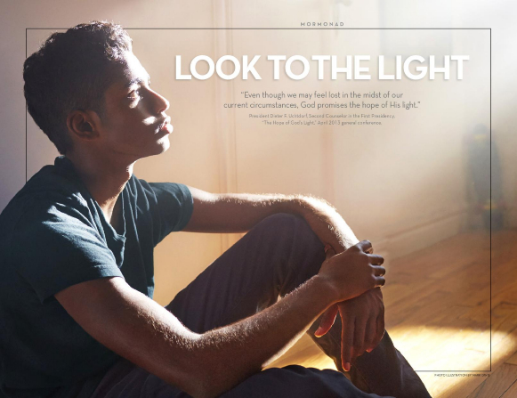 A young man sits on the floor, looking contemplatively toward a bright light.