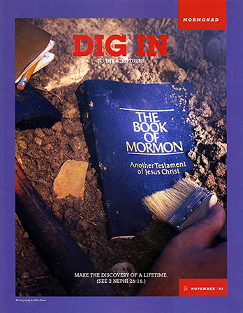 "A conceptual photograph of a hand excavating a copy of the Book of Mormon, paired with the words ""Dig In to the Scriptures."""