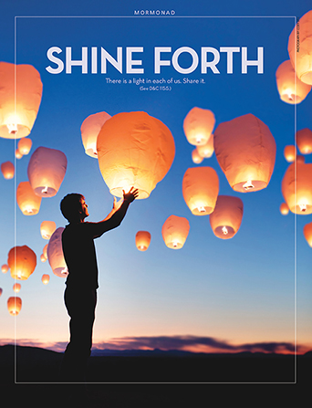 "A photo of a man standing below sky lanterns floating in the night sky, paired with the words ""Shine Forth."""