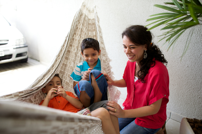 A dark-haired mother in a pink shirt laughs while she watches her children playing in a fabric hammock hanging from the ceiling.