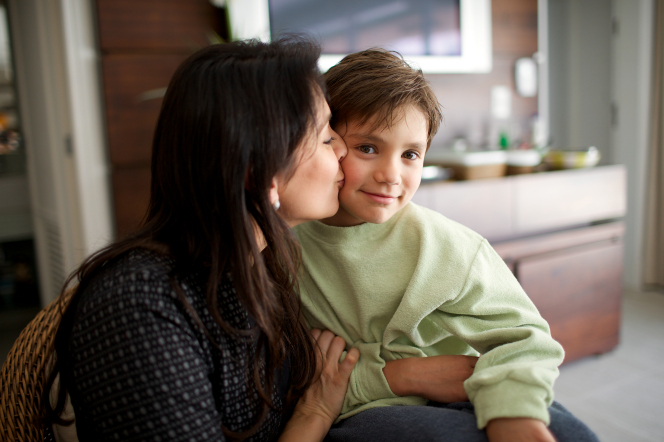 A dark-haired woman kisses her son on the cheek while he looks out at the camera.