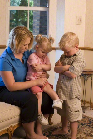 A mother sits on a couch and helps her two children pray.