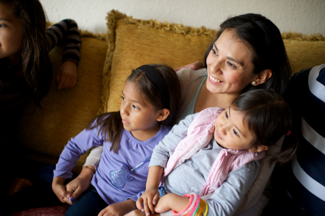 A dark-haired woman sits on a yellow couch, holding her two young daughters, who are posing for another camera that is out of the frame.
