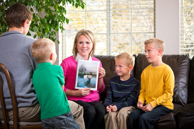 A mother shows her sons a picture of Jesus being baptized.
