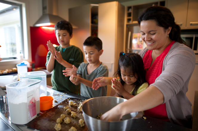 A mother bakes cookies with her three children in the kitchen.