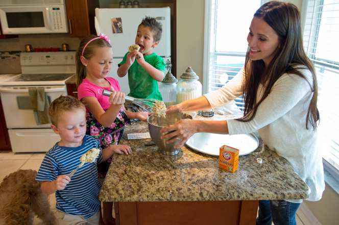 A woman and her three children make cookies in their kitchen, taking spoonfuls of dough out of a large metal bowl.