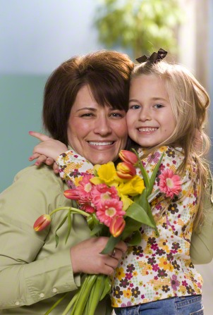 A mother hugs her daughter while holding a bouquet of flowers.