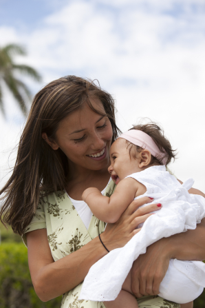 A mother in Hawaii holds her baby daughter in her arms while outside.