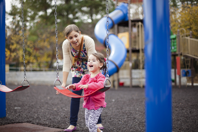 A mother bends over and helps her daughter onto a swing at a playground.