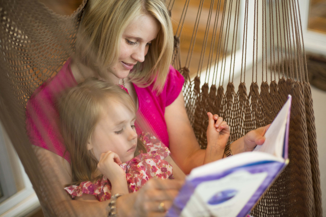 A woman with blond hair sits in a burlap hammock, holding her daughter on her lap and reading a book to her.