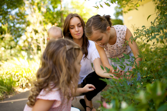 A mother picks flowers in a garden with her daughters while holding her baby.