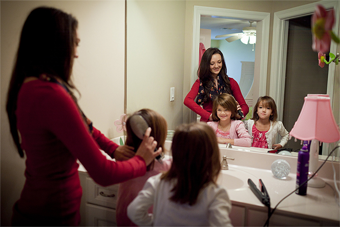 A mother stands in front of a mirror and brushes her two daughters' hair.