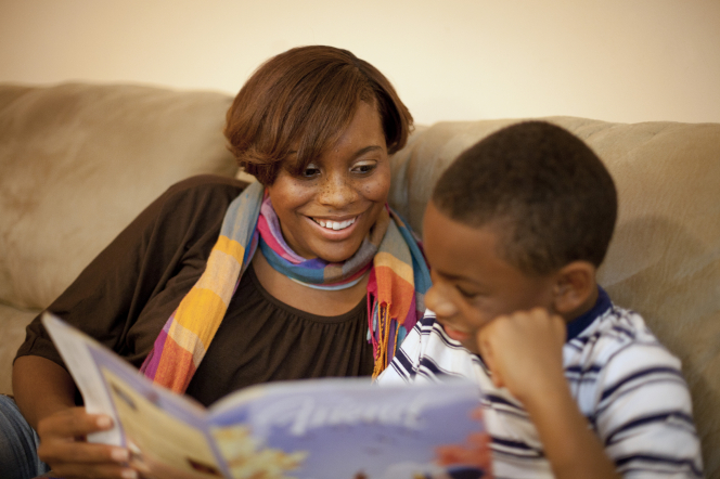A mother sits on the couch with her son and reads the Friend magazine with him.