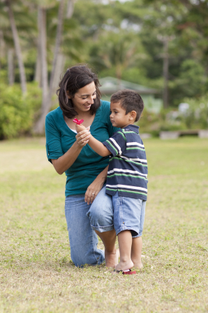 A toddler boy in Hawaii gives his mother a flower while they are outside.