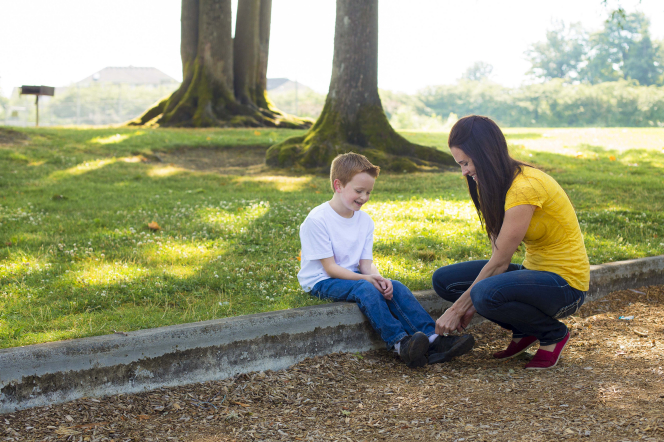 A mother helps tie her son's shoes while outside at a park.