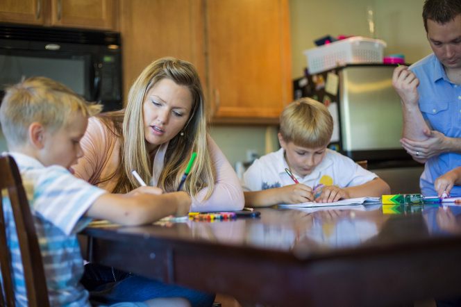 A mother and father sit at the kitchen table using markers to color with their sons.