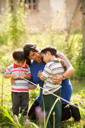 A mother kneels down next to her two sons in a garden and wraps her arms around them.
