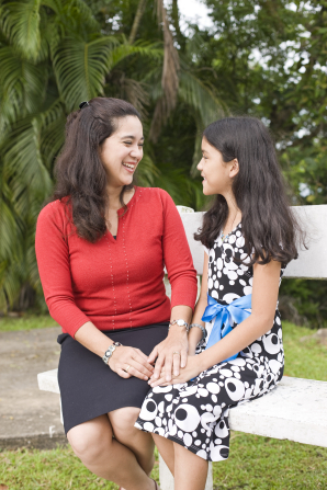A mother and daughter in Panama sit on a bench and talk together.