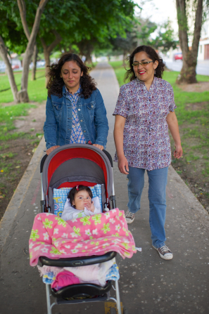 Two women in Peru walk on a path through a park and push a baby in a red stroller.