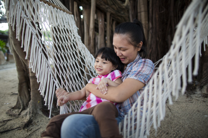 A dark-haired woman holds her daughter while the two of them sit and swing together in a white hammock near some trees.