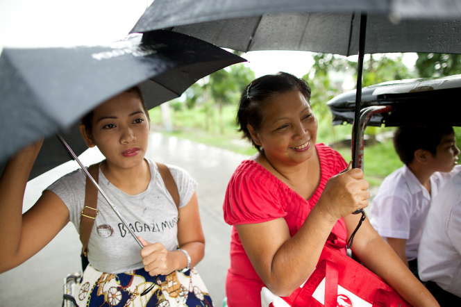 A woman in a pink shirt sits next to her daughter while they travel on a rainy day, holding black umbrellas overhead.