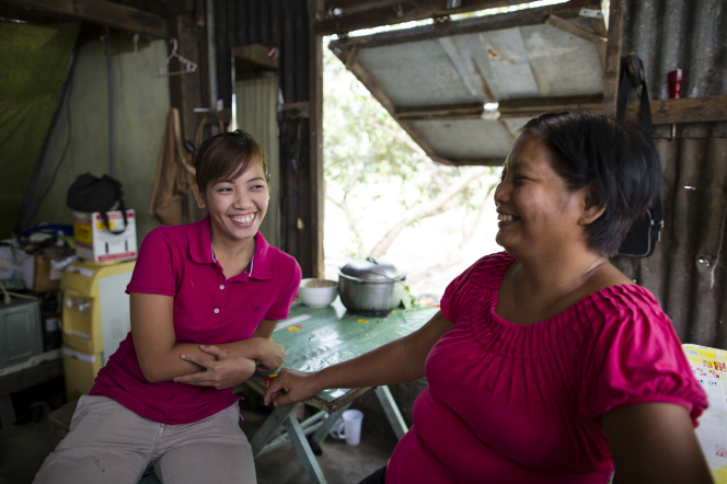 A woman and her teenage daughter, both wearing pink shirts, sit together and smile and laugh.
