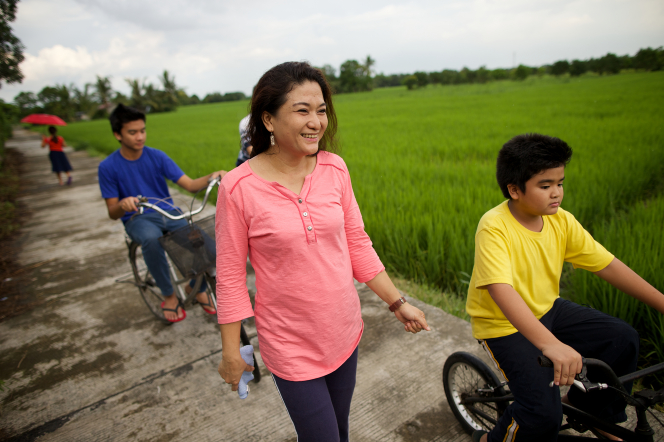 A woman in a pink shirt walks near her two sons, who are riding bicycles on a path surrounded by green fields.