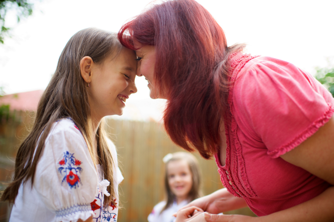 A red-haired woman presses her forehead to her daughter's face while the two of them share a laugh together.
