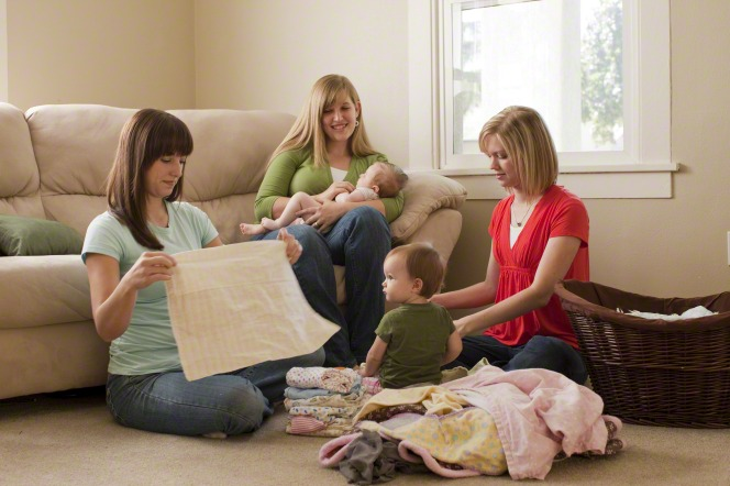 Visiting teachers fold laundry for a young mother while she holds her baby.