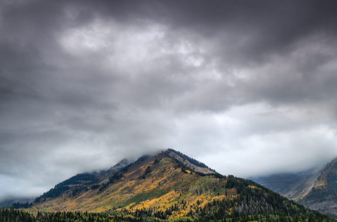 A peak in the Alpine Loop during autumn with storm clouds above.