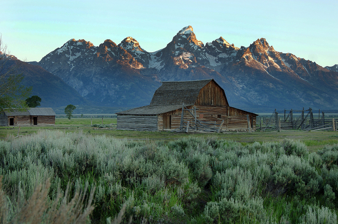 An old wooden barn with the Teton Mountains in the background.