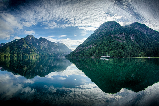 Mountains and clouds in an Alaskan lake with a boat in the water.