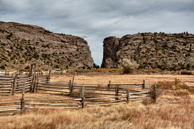 A field with a wooden fence and brush near Devil's Gate in Wyoming.