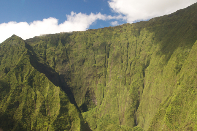 Cliffs on the island of Hawaii with a blue sky and clouds above.