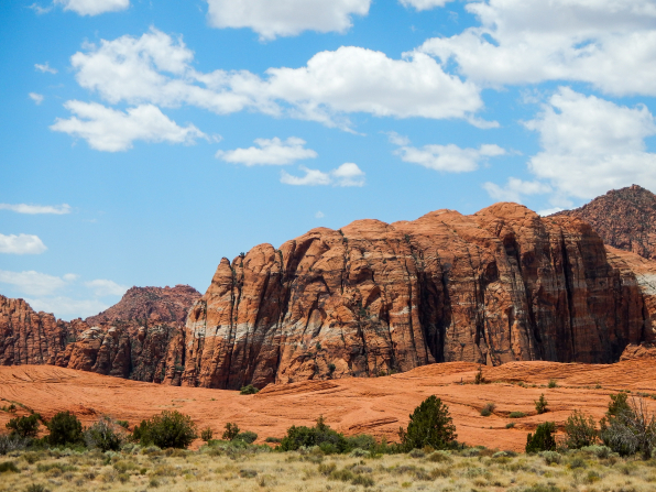 High rock formations against a blue sky with clouds at Snow Canyon State Park in southern Utah.