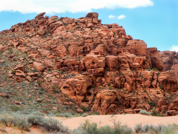 Red rocks lined with green brush and a blue sky in Snow Canyon State Park in southern Utah.