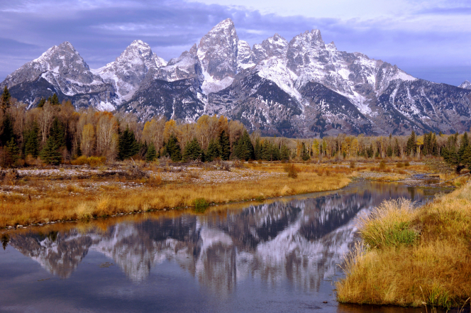 The Teton Mountains topped with snow, reflected in a river in Wyoming.