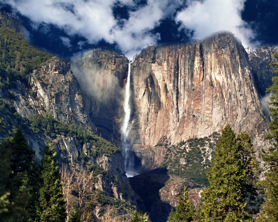A large waterfall over a cliff bordered by trees and a blue sky in Yosemite National Park.