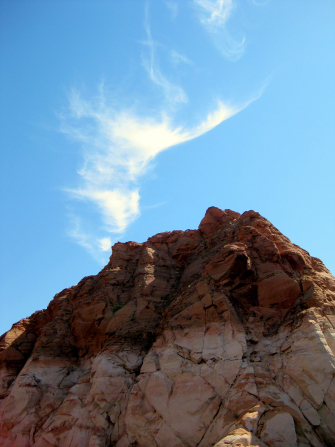The top of a red rock mountain in southern Utah with a blue sky above.