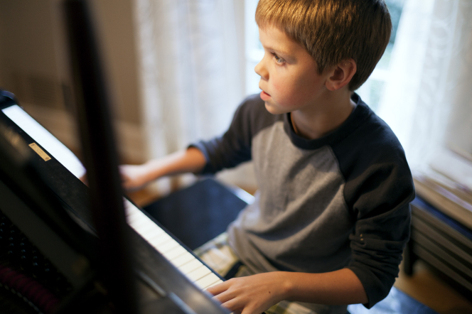 A young boy sits down on a piano bench, playing the piano.